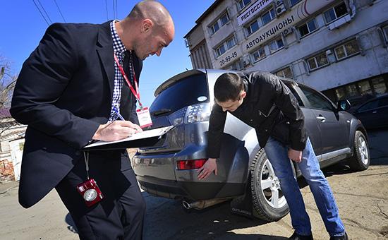 Сотрудник страховой компании фиксирует повреждения автомобиля