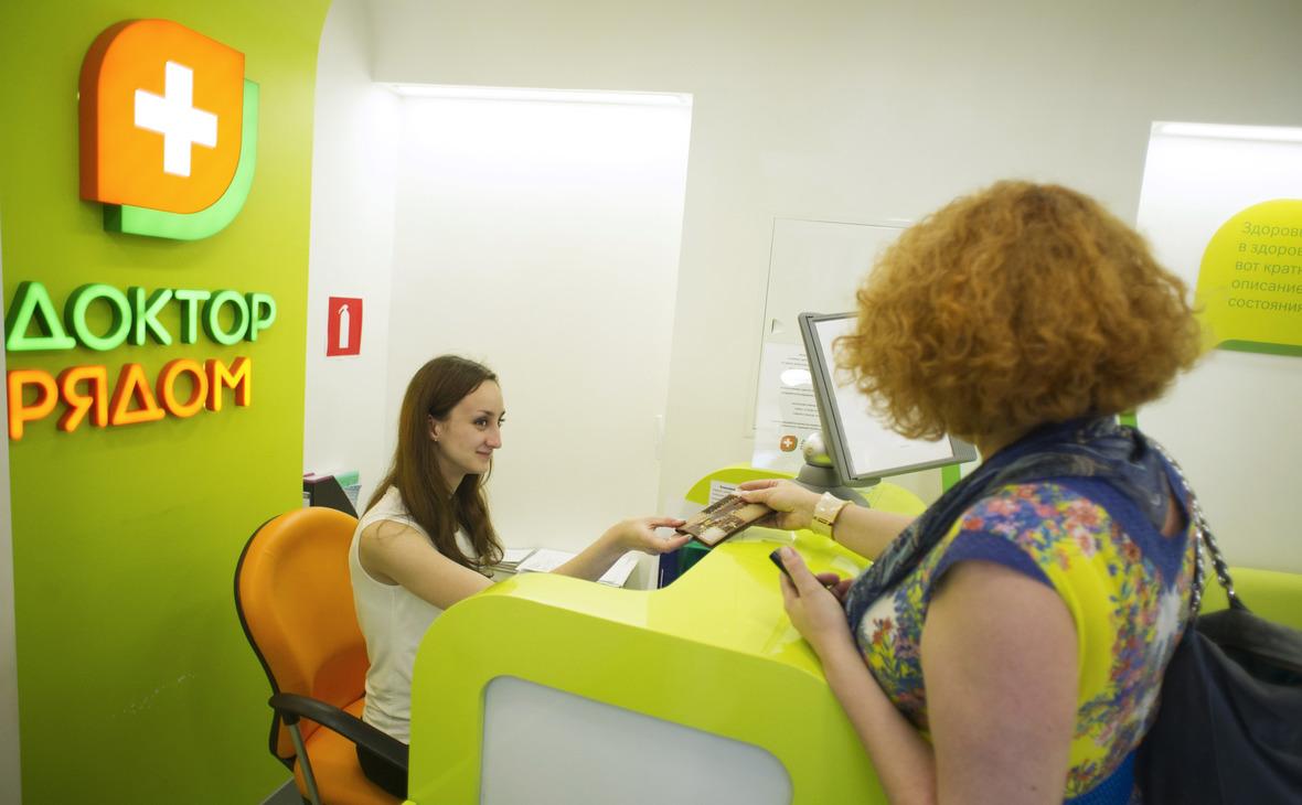 Посетительница у стойки регистратуры в клинике по проекту «Доктор рядом» на проспекте Защитников Москвы