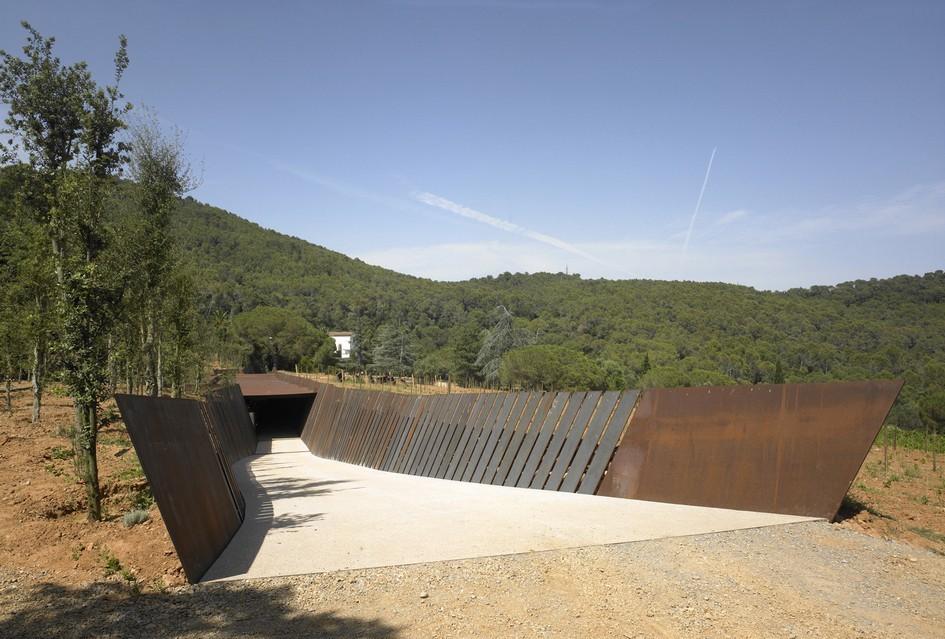 Стены постройки, через которые проступает дневной свет, наклоняются в разные стороны, создавая динамический эффект