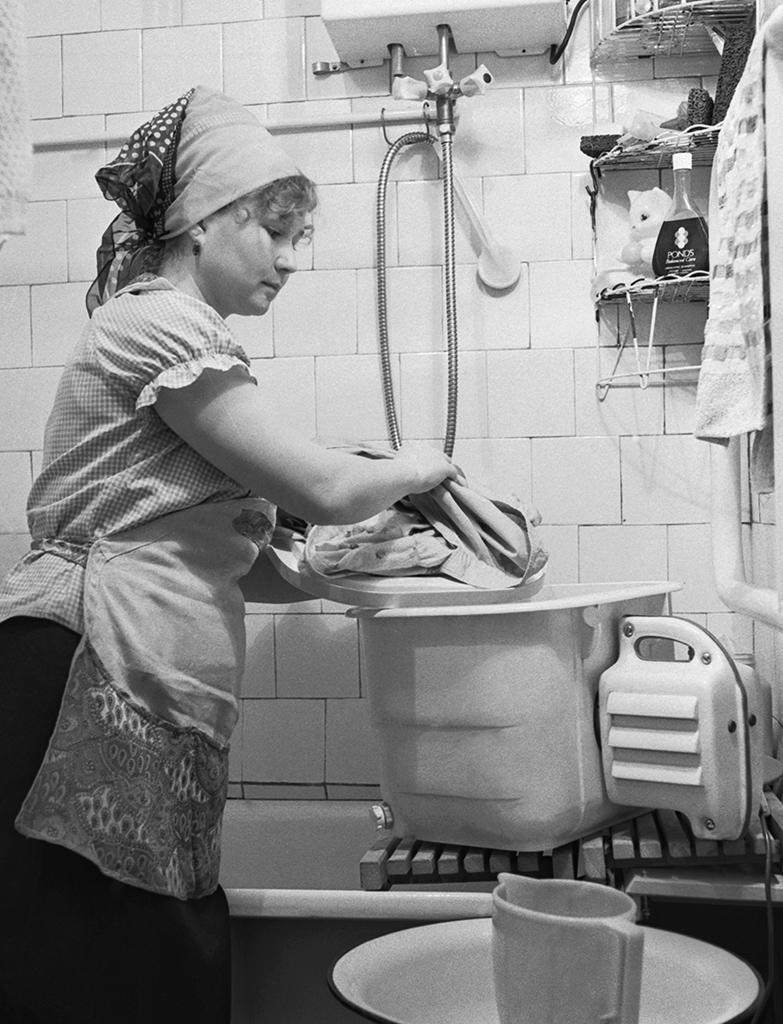 Санузлы в 1980-е  В типовых хрущевках и блочных девятиэтажках площадь ванной составляла всего 2 кв. м, а туалета — 1 кв. м. В кирпичных пятиэтажках советского домостроения совмещенный санузел размещался на площади 3 кв. м. Во многих квартирах нельзя было поставить полноценную ванну, и жильцам приходилось довольствоваться «сидячими» аналогами  На фото: стиральная машина «Малютка». Дата съемки: 01.02.1984