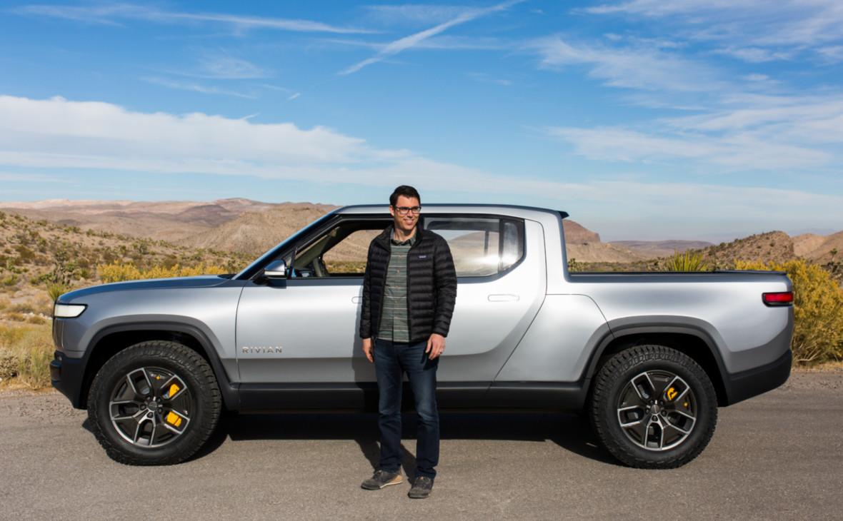 Основатель и генеральный директор Rivian Automotive Ар-Джей Скаринджна фоне электрического пикапа R1T