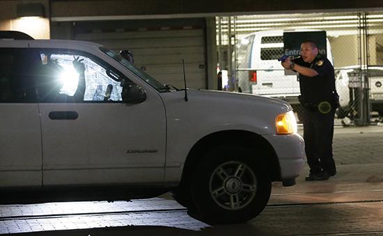 Полицейский задерживает водителя вовремя стрельбы вДалласе. 7 июня 2016 года  
