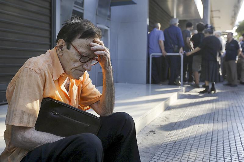 77-летний мужчина около отделения Национального банка Греции ждет своей очереди, чтобы попытаться забрать пенсию