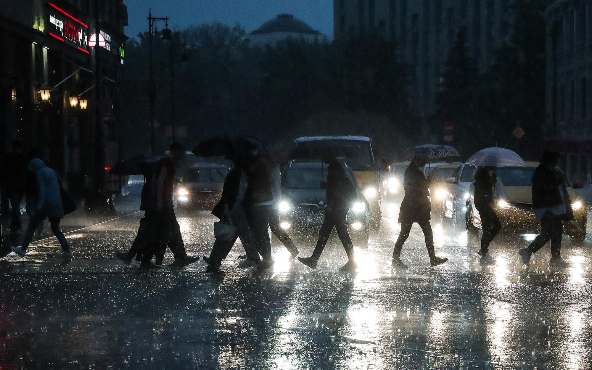 Горожане на пешеходном переходе во время дождя на одной из улиц города