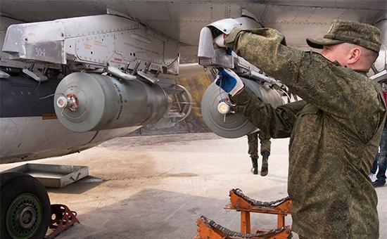 Авиатехник устанавливает бомбы напилоны российского самолета на базеХмеймим ВКС РФвСирии