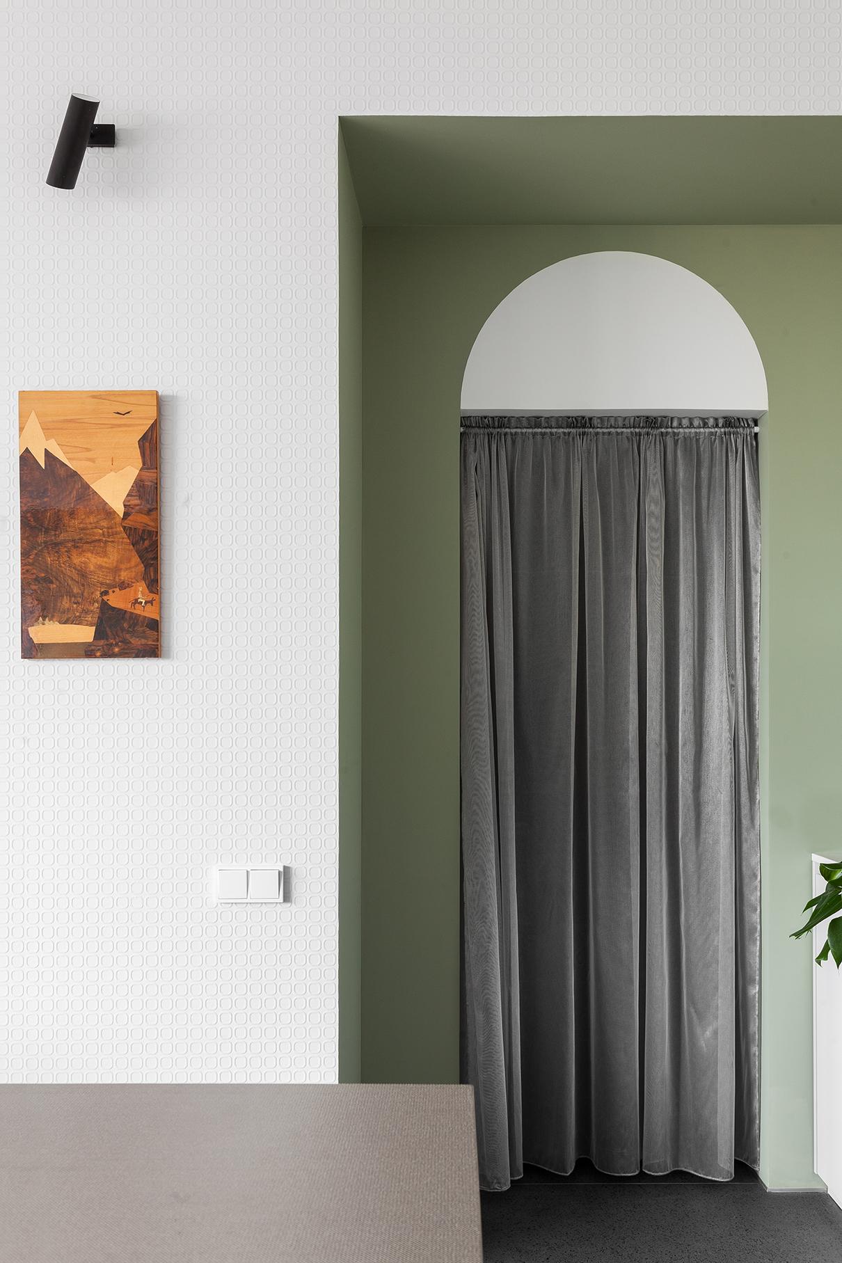 Часть стен в квартире оклеена обоями под покраску с мелким рисунком, напоминающим по форме старые ламповые телевизоры. Картина в технике маркетри на стене— винтажный декор из коллекции DVEKATI. Над ней— бра Faro