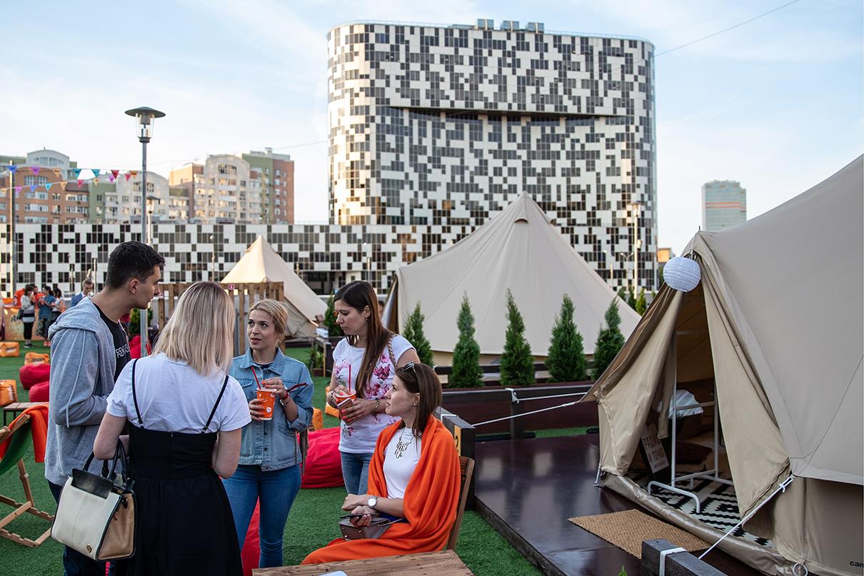Посетители на территории палаточного городка Moscow Escape Glamping на крыше торгового центра «Авиапарк». Глэмпинг Moscow Escape Glamping— зона отдыха с палатками, совмещающая в себе отдых под открытым небом и гостиничные удобства