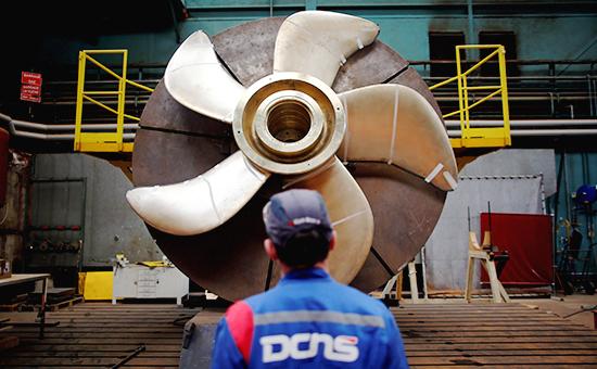 Рабочий компании DCNS смотрит нагребной винтподлодки класса Scorpène