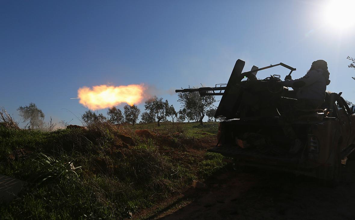 Поддерживаемые Турцией сирийские боевики ведут огонь на линии фронта в провинции Идлиб