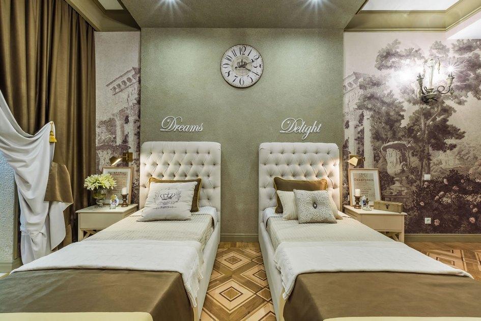 В центре комнаты находится спальная зона сдвумя одинаковыми кроватями