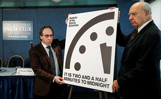 Председатель Бюллетеня ученых, работающих в атомной отрасли, Лоуренс Краусс (слева) возле «часов судного дня»