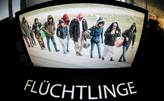 На мониторе мигранты напути изАвстрии вГерманию. Ниже немецкое слово Flüchtlinge (беженцы), которое названо словом года вГермании