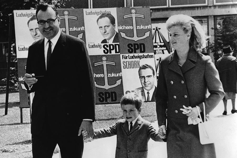 Глава федеральной земли Рейнланд-Пфальц Гельмут Коль сосвоей первой женой Ханнелорой Коль исыном проходят мимоизбирательных плакатов социал-демократов вЛюдвигсхафене. 8 июня 1969года.