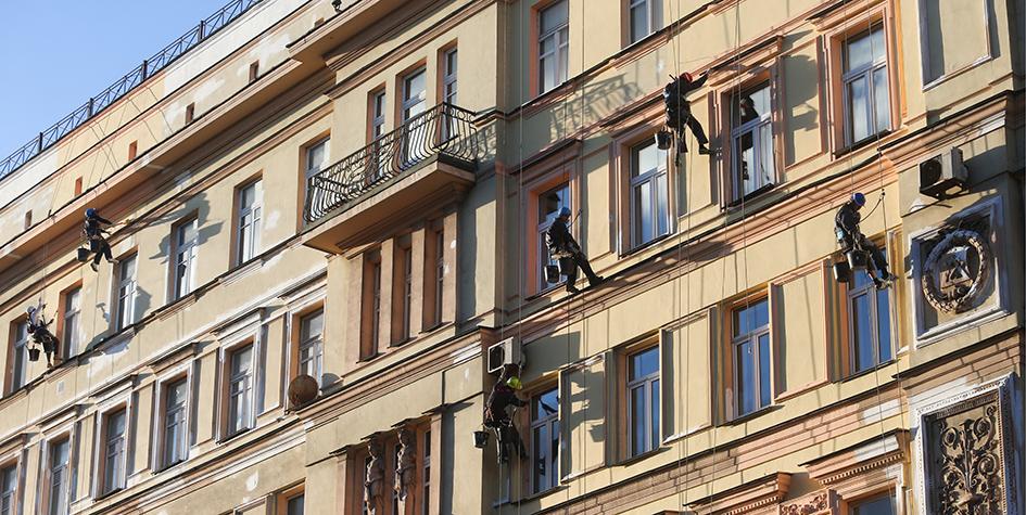 Рабочие во время работ по благоустройству фасада дома на Тверской улице