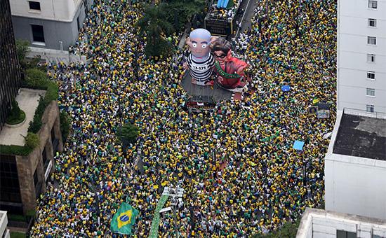 Надувные фигуры бывшего президента Луиса Инасиу Лулы де Сильва(слева) и действующего президента Бразилии Дилмы Русефво время протеста на улице Сан-Паулу