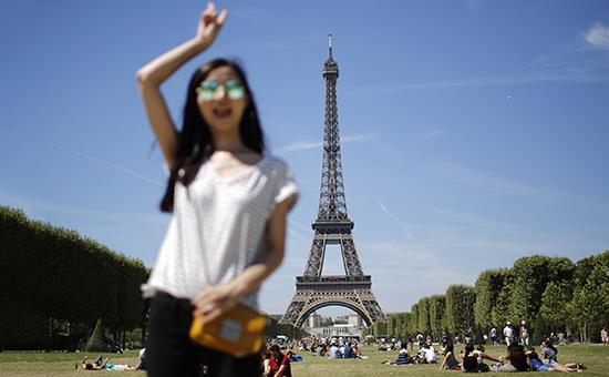 Туристка у Эйфелевой башни в Париже