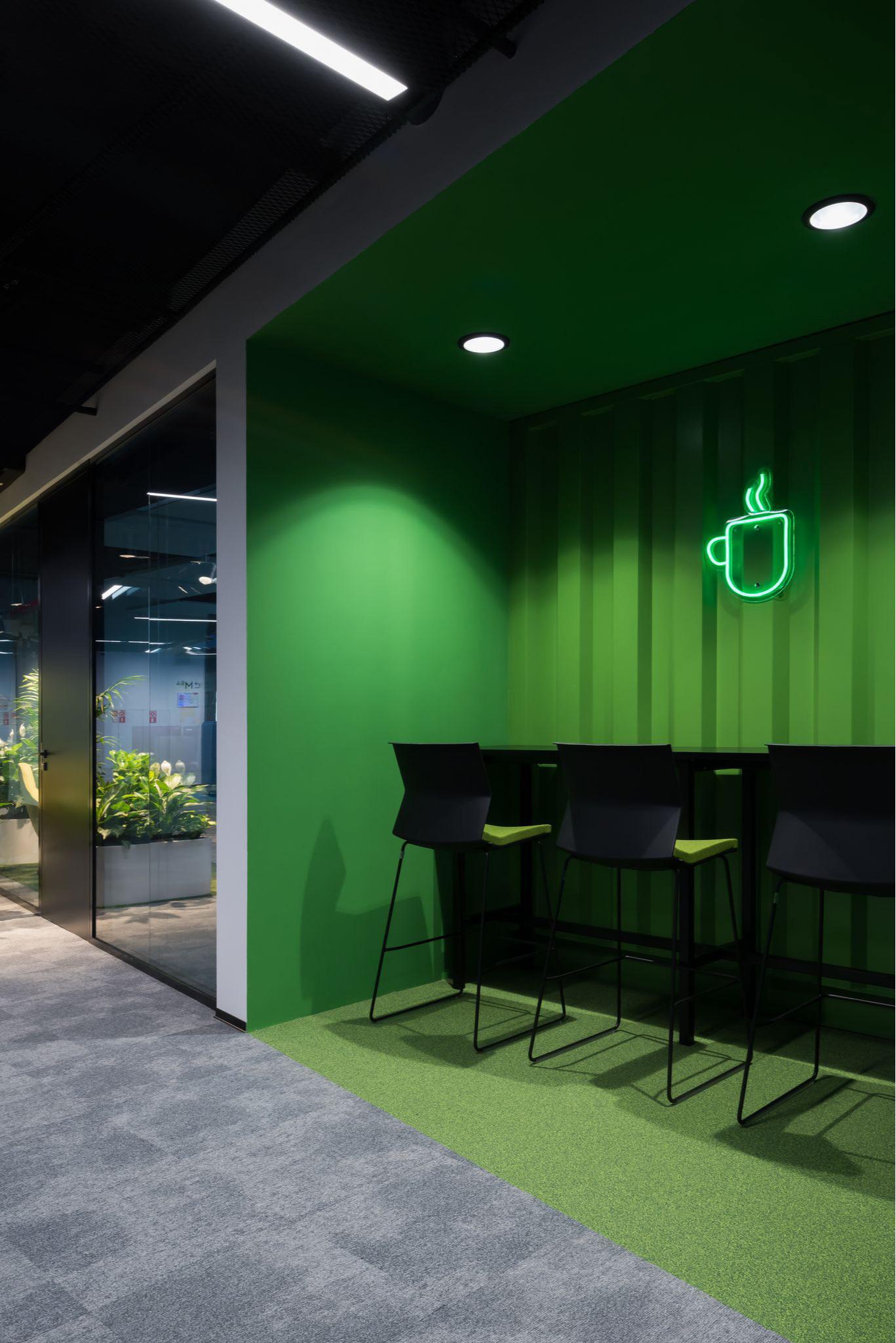 Зона неформального общения для уединенной работы или кофе-брейка выполненная в зеленом цвете. На стене установлена неоновая вывеска в виде кружки.