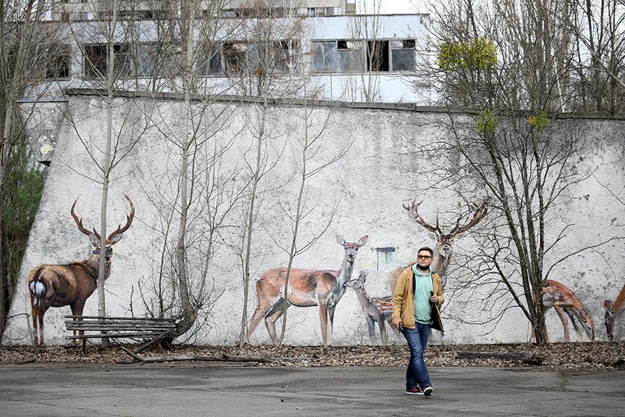Мужчина прогуливается в Припяти, апрель 2021 года