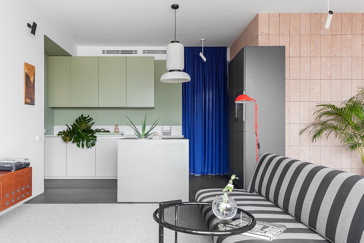 Кухня и остров-куб произведены по чертежам DVEKATI, цвет навесных шкафов из МДФ подобран в цвет стены, чтобы максимально их растворить. Из этогоже материала— поднос на столешнице, изготовленный по эскизам архитекторов по просьбе заказчицы. Куб облицован керамикой и имеет потайные шкафчики для хранения и отверстие-кашпо для живых растений. За синей шторой в проеме— приватная часть квартиры: две спальни, хозяйская ванная и постирочная. Картина в технике маркетри на стене— винтажный декор из коллекции DVEKATI. Светильник над кубом— Formakami, дизайн Хайме Айона для &Tradition. Подвесные направленные светильники— Faro. Тумба под музыкальным проигрывателем с металлическими клепками— конструктивная разработка и дизайн DVEKATI