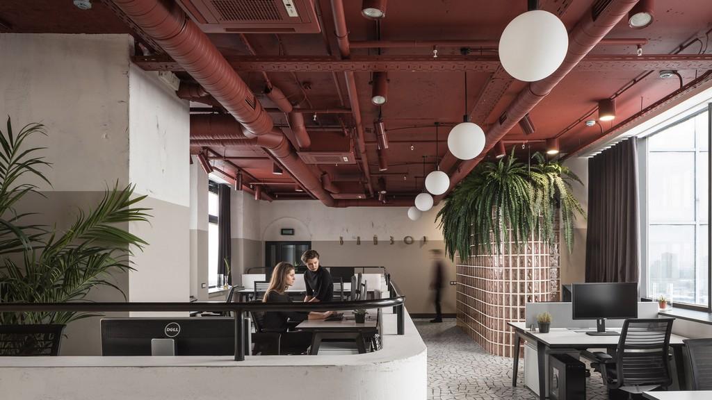 Входная зона офиса оформлена ввидерозовых стеклянных блоков, которые украшены висячими растениями—такие можно было увидеть почти вкаждом советском учреждении