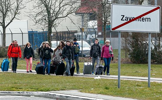 Люди покидают аэропорт Брюсселя, гдепроизошло два взрыва