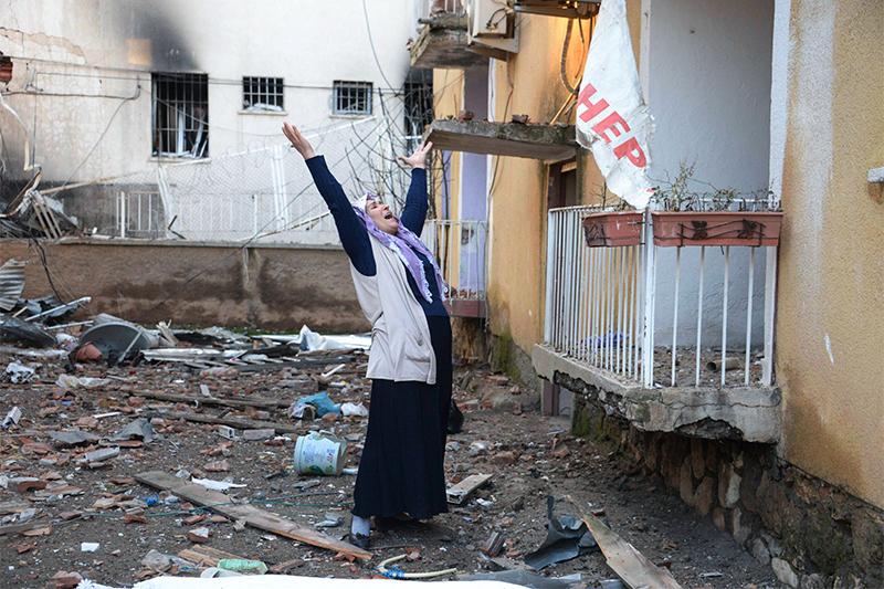 Кричащая женщина у разрушенного взрывом полицейского участка