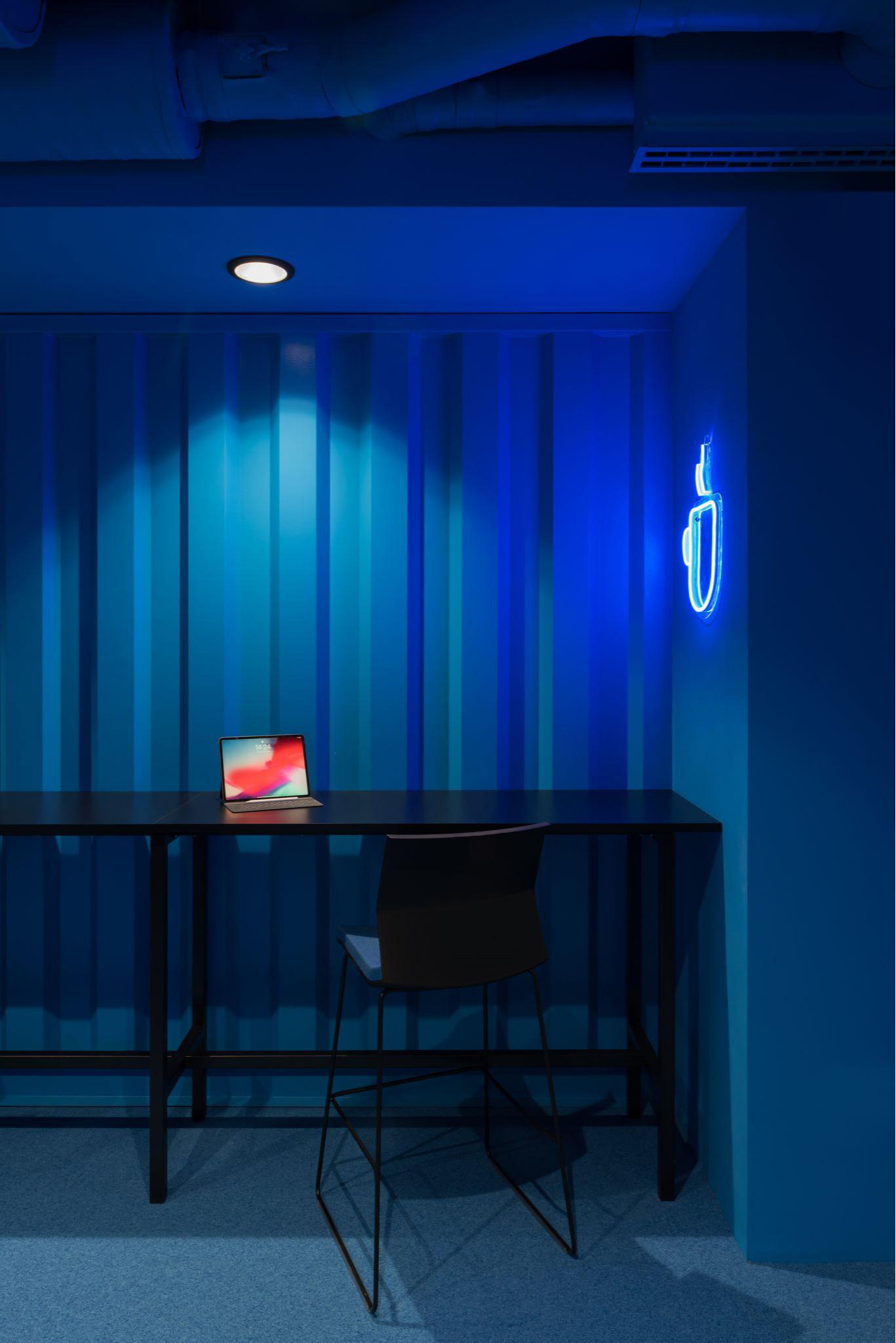 Зона неформального общения выполнена в синем цвете. На стене установлена неоновая вывеска в виде кружки.