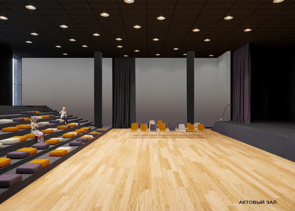 Актовый зал — центр школы, место ежедневного сбора родителей и детей, проведения уроков и перемен — без обычных для него тяжелых кресел, а лишь со ступенями и подушками