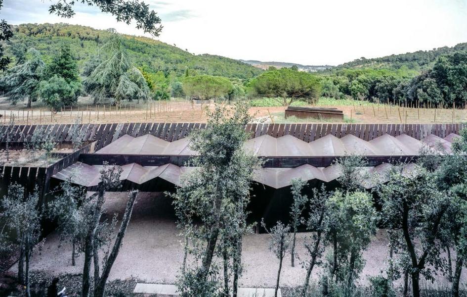 Здание этой частной винодельни, расположенное у подножия горы, выполнено из черной стали и дерева и словно врыто в землю, повторяя изгибы холмистого паламосского ландшафта