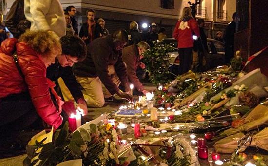Принесенные парижанами цветы исвечи на месте убийства у ресторана Сarillon