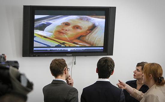 Журналисты смотрят на экран телевизора, по которому показывают допрос российского гражданина  Александра Александрова