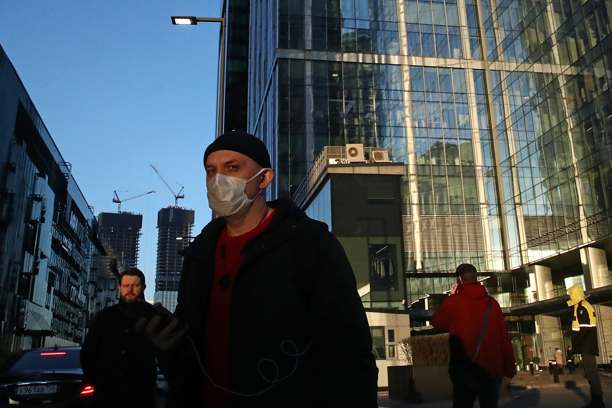 Мужчина в защитной маске на фоне Московского международного делового центра «Москва-Сити» во время пандемии коронавируса COVID-19