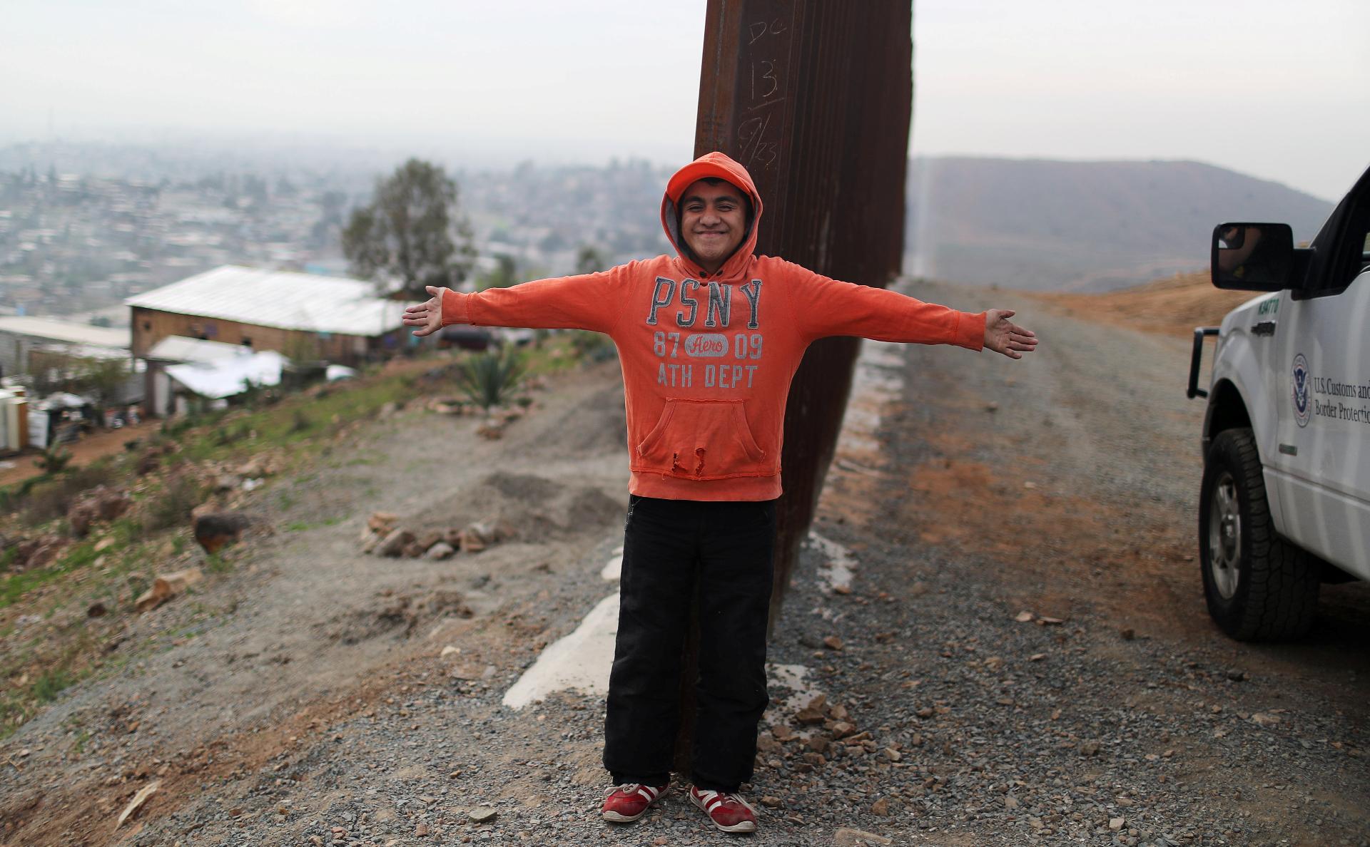Мексиканский юноша фотографируется на границе с США — в том месте, где оканчивается стена