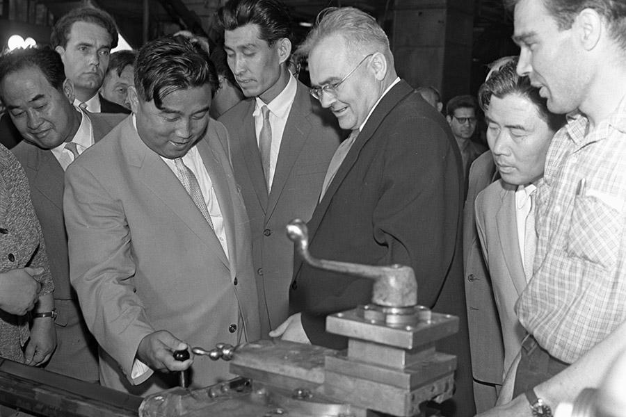 В 1956 году лидер КНДР Ким Ир Сен совершил большую поездку по СССР и странам Восточной Европы. Там он встретился с Никитой Хрущевым и другими партийными руководителями, которые говорили ему «о необходимости преодоления культа личности в КНДР, развитиивнутрипартийной демократии».  Одной из целейпоездки былисписание долга КНДР по поставкам военного времени, договор о поставках в страну товаров и техники. Советское правительство сочло возможным «оказать помощь в разрешении вопросов, поставленных правительственной делегацией КНДР без каких-либо условий».  Кроме Москвы Ким Ир Сен побывал и в Свердловске (сегодня — Екатеринбург), где посетил Уралмашзавод. По такому случаю город был украшен флагами КНДР, а в Театре музыкальной комедии прошла премьера оперетты «Белая акация».