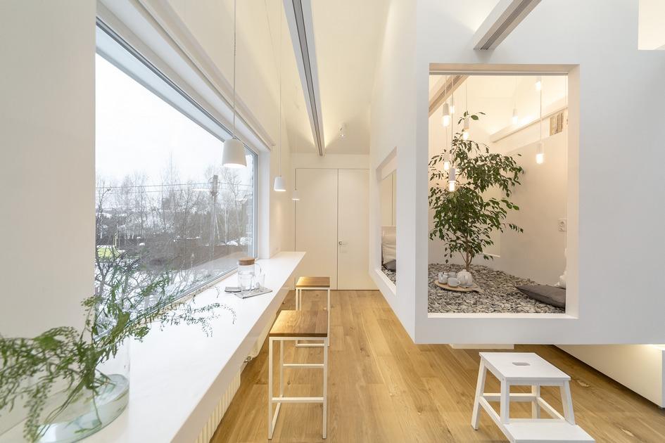 Дизайнеры из студии Ruetemple поместили в центр мансардного помещения куб с галькой и живым деревом