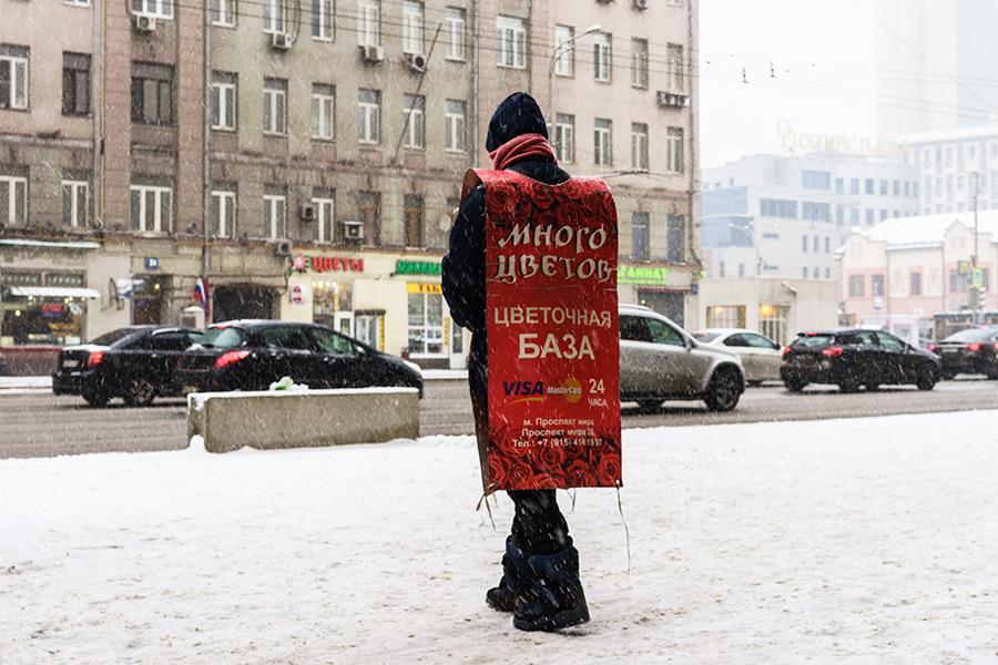Зазывала  Важный участник цветочного рынка—зазывала. В Москве они есть практически у всех крупных цветочных сетей. Цель зазывал—показать покупателям, чтонеподалеку есть цветочный магазин, иуказать, гдеименно, так каксами магазины-склады, какправило, располагаются водворах илиподвалах.  Герой кадра приехал научебу изАфрикиитеперь прячет лицо затолстым шарфом отхолода. Его доход—рубль закаждую листовку. За час он должен раздать 150 штук. Всегожеего рабочий день длится семь часов.