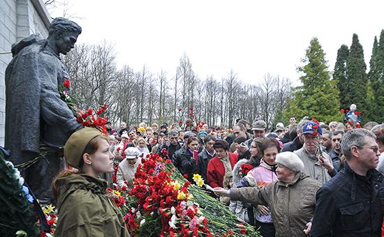 Жители Таллина возлагают цветы кБронзовому солдату наВоенном кладбище, кудаон был перенесен в2007 году