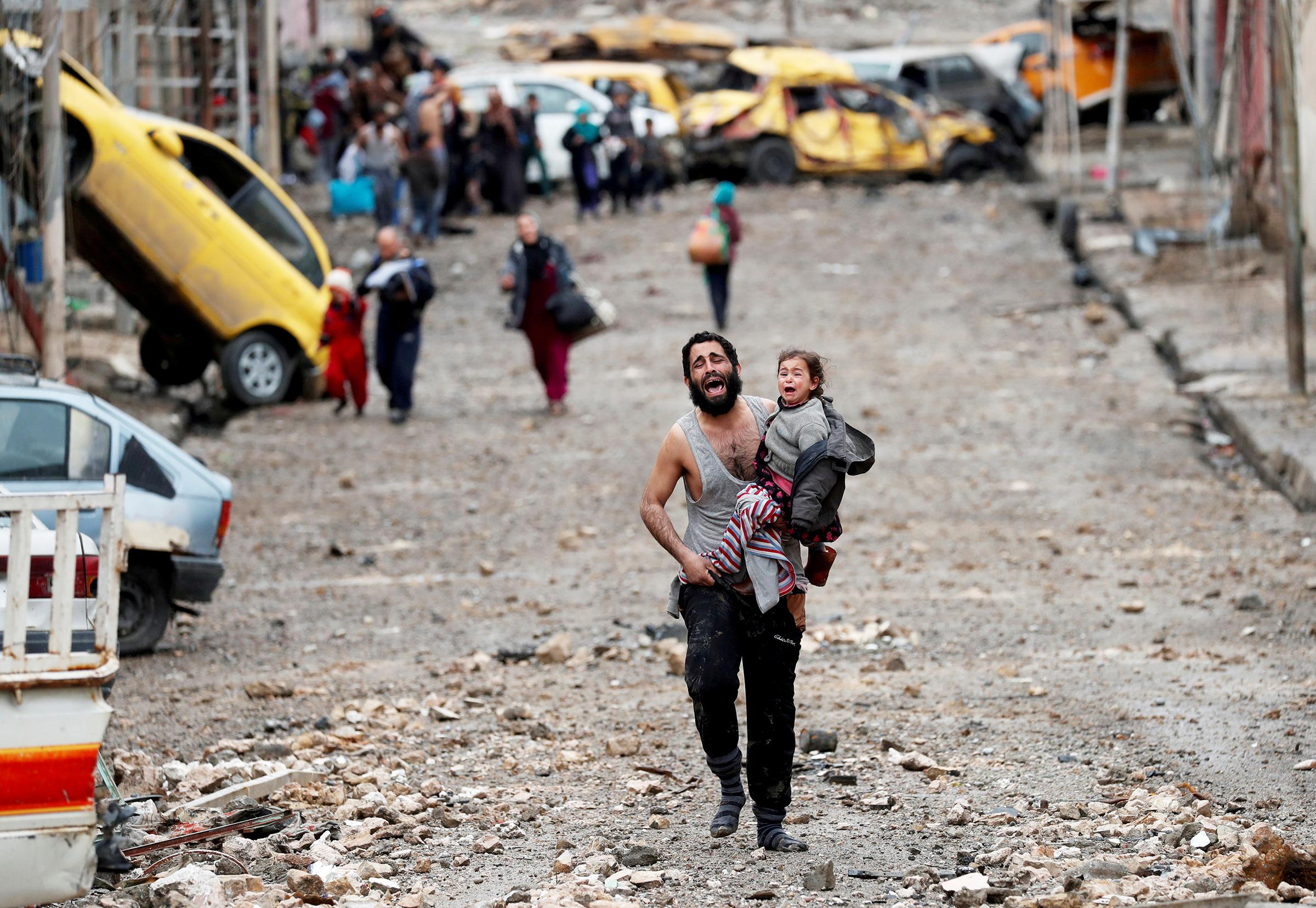 Автор фото Горан Томашевич: «Оба, отец и дочь, в ужасе бежали по разбитой улочке Вади-Хаджара, за мгновение превратившегося в поле битвы между солдатами ИГ и иракскими спецслужбами.  Они и их соседи — кто-то в сандалиях, а кто-то босиком — спасались, убегая от пуль. <…> Отец был не в себе, он был в панике. Он очевидно не был террористом. Мне хотелосьбы верить, что оба они добрались до лагеря беженцев».