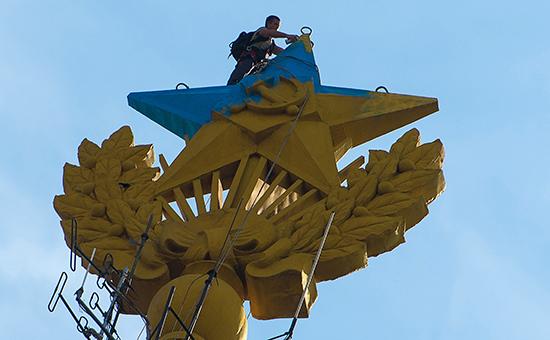 Рабочий реставрирует звезду, которую раскрасили руферы. Август 2014 года
