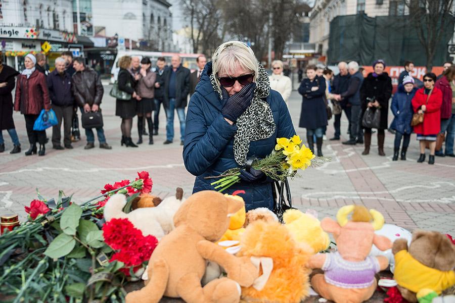 Жители Симферополя возлагают цветы к мемориалу на площади Ленина в память о погибших в ТЦ в Кемерово
