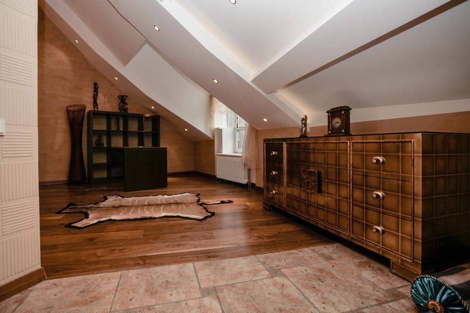 На полу — симулякр медвежьей шкуры, вдоль стен — мебель, часы и подушки в восточном стиле