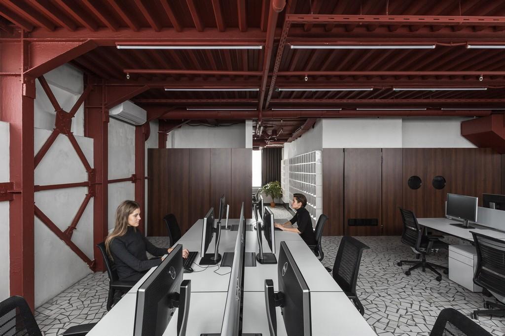 Одна рабочая зона выделена невысокими стеклянными перегородками, стены другой выполнены из деревянных панелей
