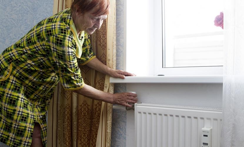 Местная жительница показывает, как регулировать уровень отопления в батарее