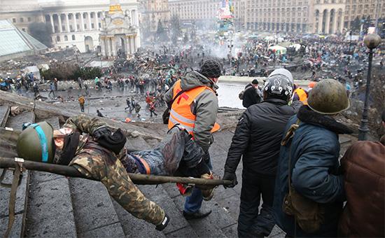 Протестующие несут раненого товарища, во время беспорядков со стрельбой на Майдане в Киеве, 20 февраля 2014 года