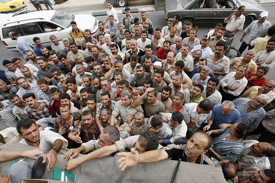 Безработные палестинцы в очереди за пособием в Газе