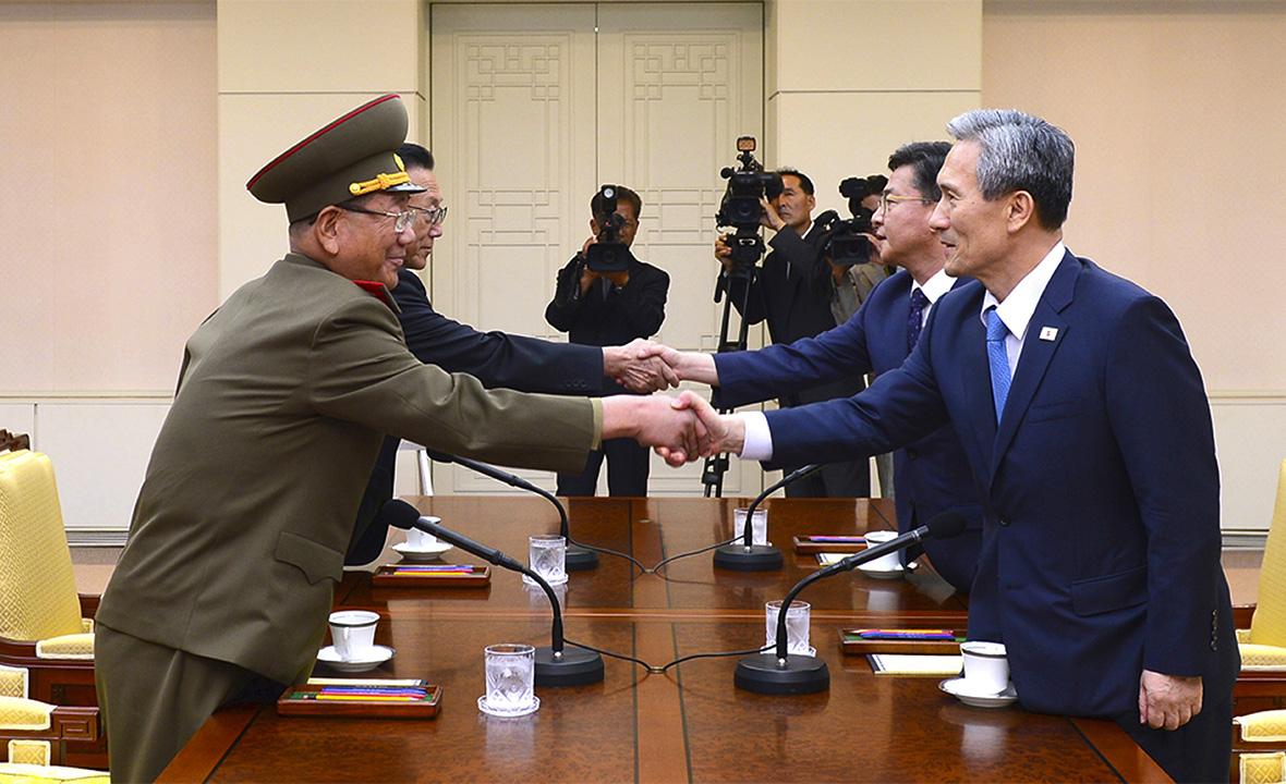 Высокопоставленный офицер армии КНДР Хванг Пиенг(слева) и министр обороны Республики Корея Ким Гванджин (справа) во время встречи в деревнеПханмунджом на границе двух государств. 22 августа 2015 года