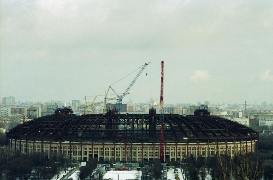 В 1996–1997 годах «Лужники» пережили самую масштабную реконструкцию, в результате которой на арене появилась крыша. Над трибунами оборудовалинавес, а скамейки для зрителей заменили пластиковыми креслами  На фото: вид на стадион «Лужники» с Воробьевых гор. Смонтирована последняя балка в перекрытии раздвижной крыши стадиона «Лужники». 1997 год