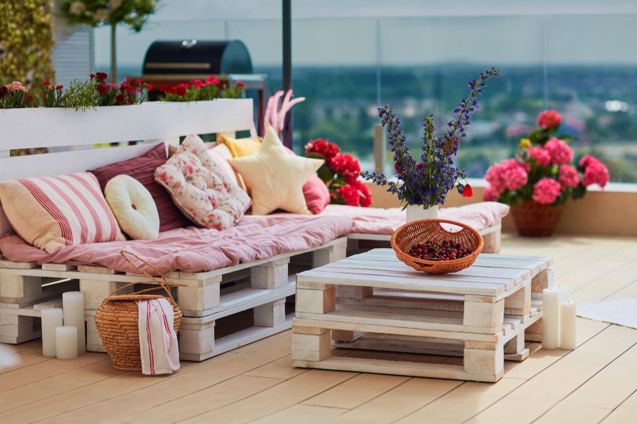 Недорогой вариант обустройства дачной лаундж-зоны — это мебель из строительных поддонов. Ее можно собрать самим, покрасить или покрыть маслом