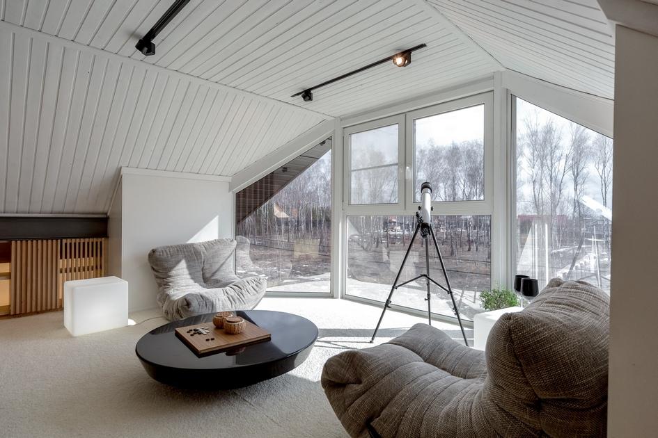 Мансарда с панорамным остеклением от студии Lofting имеет собственный камин