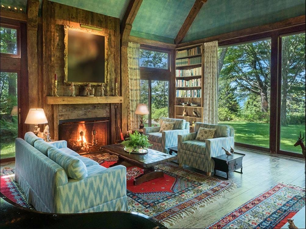 В гостиной с двумя каминами установлены окна от пола до потолка. Из них открывается вид на залив и окружающий сад